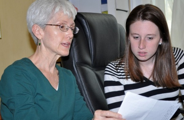 Becky Roberts explains to volunteer Katie Strickland how to record residents' medicine use.