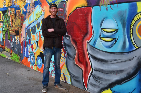 Clay Wooten stands in front of the Art Alley.