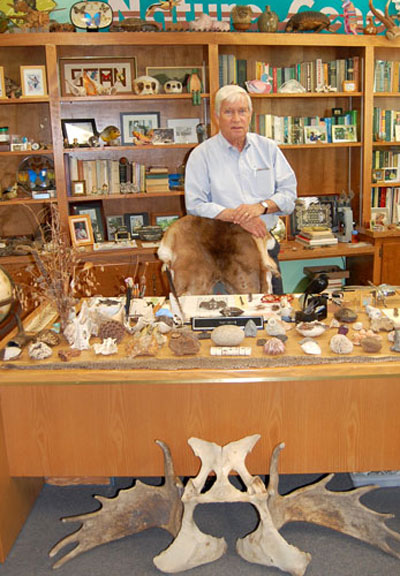 Rudy Mancke standing among specimen in his office