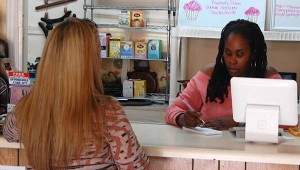 Folami Geter, owner and head chef at Lamb's Bread vegan cafe, takes an order from a customer. Geter prides herself on offering customers a warm and friendly dining experience.
