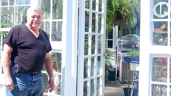Russell Long in front of his greenhouse.