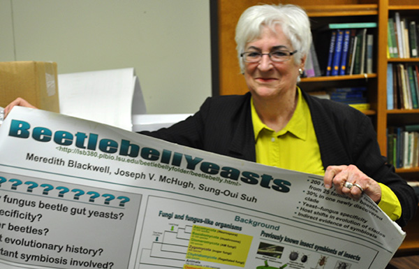 Meredith Blackwell holds up a scientific poster.