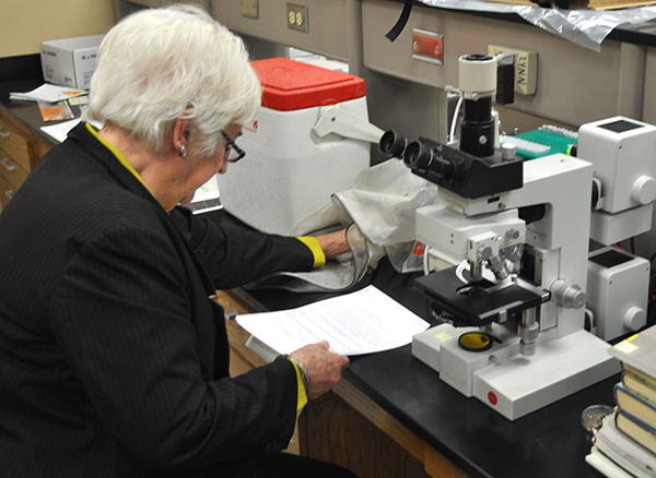 Meredith Blackwell sits at a microscope.